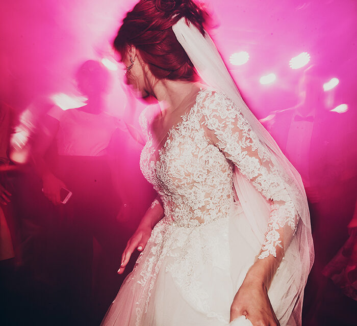 stylish happy bride dancing at wedding reception. gorgeous wedding couple having fun and partying in restaurant in light show. newlywed emotional moment. space for text
