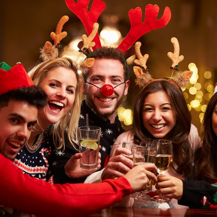 Group Of Friends Enjoying Christmas Drinks In Bar Smiling To Camera